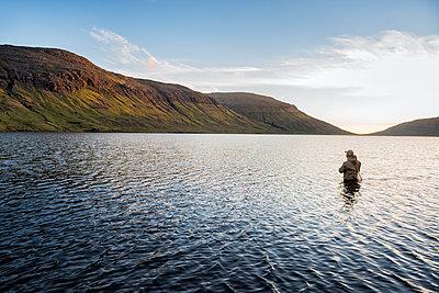 Man fishing in lake - p312m2051448 by Hans Berggren