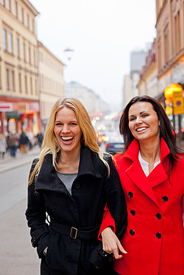 Two female friends walking together in street - p312m695946 by Conny Fridh