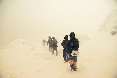 Caucasian hikers walking on snowy path - p555m1410827 by Aleksander Rubtsov