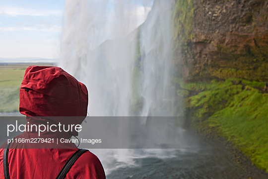 Woman admiring the waterfall Seljalandsfoss in south Iceland - p1166m2279421 by Cavan Images