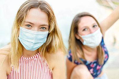 Female friends wearing protective face masks outdoors - p300m2252438 by Ignacio Ferrándiz Roig