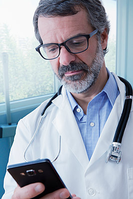Hispanic doctor texting on cell phone - p555m1232011 by REB Images