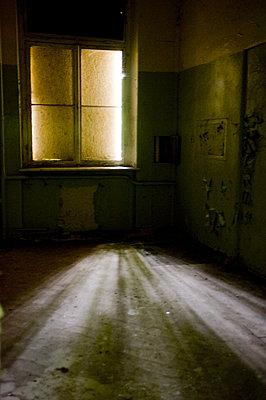 Beelitz Sonnenstrahlen durch verbarrikatiertes Fenster kommend in Raum einer alten Krankenhausanlage - p627m1035580 von Samantha Dietmar
