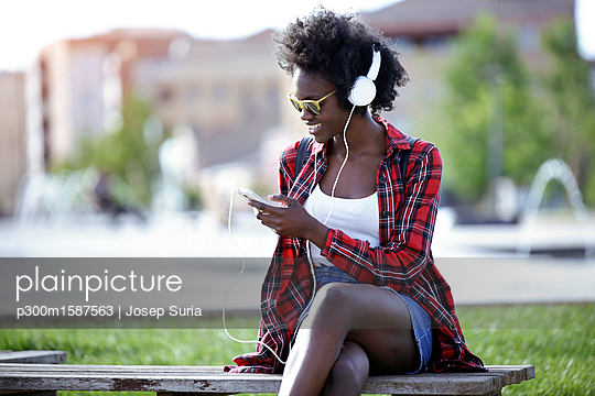 Smiling young woman sitting on bench in city park listening music with headphones - p300m1587563 von Josep Suria
