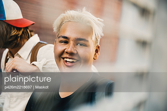 Portrait of smiling teenager with friend standing in city - p426m2218697 by Maskot