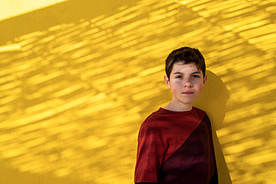 Portrait of cheerful teen leaning on yellow wall while looking camera - p1166m2152274 by Cavan Images
