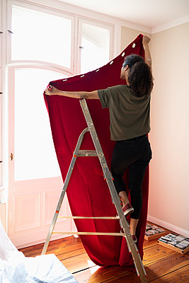 Woman on ladder hanging red curtain - p1192m2016659 by Hero Images