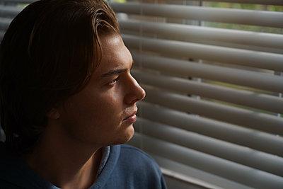 Junger Mann vor heruntergelassener Jalousie - p1694m2291652 von Oksana Wagner