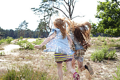 Rear view of two girls running through dune landscape - p300m2102664 by Antje Merkel