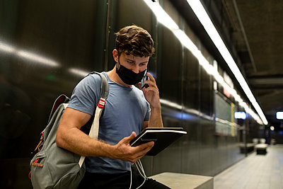 Young man wearing protective face mask talking on phone while holding digital tablet at subway during pandemic - p300m2221740 by Valentina Barreto