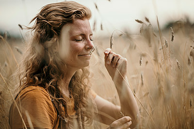Woman smelling crop while sitting in agricultural field - p300m2240908 by Malte Jäger