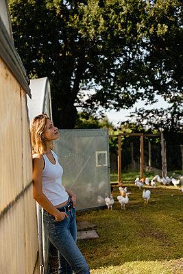Junge Frau steht gedankenversunken auf Hühnerhof - p432m2293154 von mia takahara