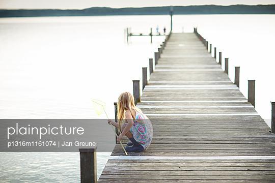 Mädchen hockt mit einem Kescher auf einem Steg, Starnberger See, Oberbayern, Bayern, Deutschland - p1316m1161074 von Jan Greune