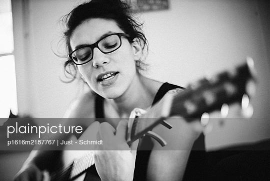 Frau spielt Gitarre, Portrait - p1616m2187767 von Just - Schmidt