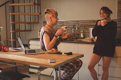 Lesbian couple having coffee in kitchen - p1315m2017984 by Wavebreak