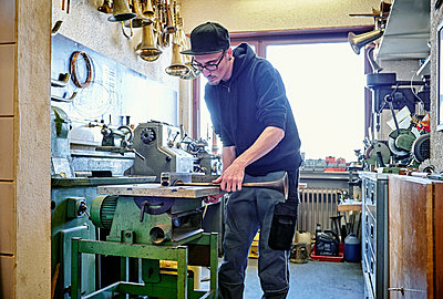 Instrument maker making trumpet in workshop - p300m1157128 by Dirk Kittelberger