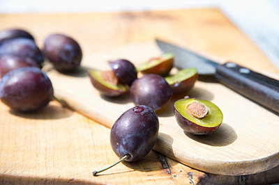 Purple plums on wooden cutting board - p300m2131733 by Achim Sass