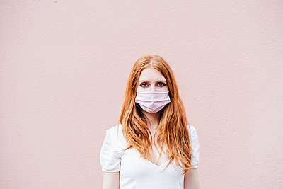 portrait of beautiful redhair woman over pink wall weraring face mask, Madrid, Spain - p300m2274546 von Eva Blanco