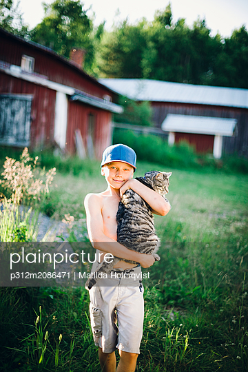 Boy holding cat - p312m2086471 by Matilda Holmqvist