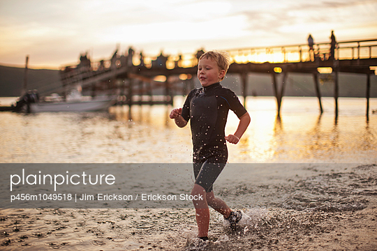 Young boy running along a beach at sunset - p456m1049518 by Jim Erickson / Erickson Stock