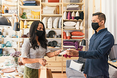 Masked shopper and store owner making purchase with credit card - p1166m2208522 by Cavan Images