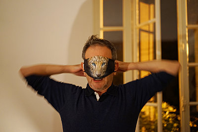 A man plays with a facial cloth mask at a party - p1610m2211229 by myriam tirler