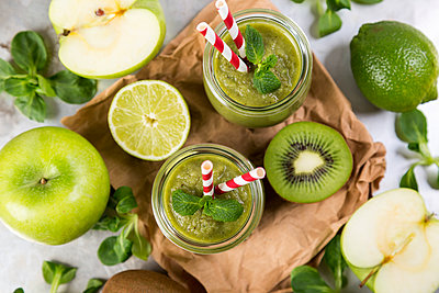 Two glasses of green smoothie and ingredients - p300m1228308 by JLPfeifer