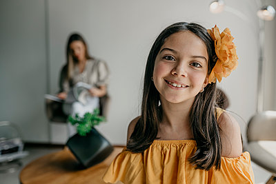 Cute girl with flower on head in waiting area while mother sitting in background - p300m2251135 by MORNINGVIEW AGENCY