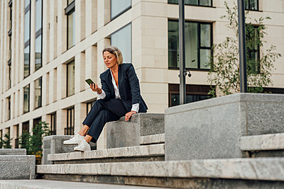 Businesswoman using mobile phone while sitting on steps - p300m2293887 by Vasily Pindyurin