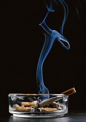 Ashtray with cigarette butts and lit cigarette smoking against black background - p62316913f by Christian Zachariasen