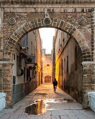 Morocco, Marrakesh-Safi (Marrakesh-Tensift-El Haouz) region, Essaouira. A person rides a bicycle through a dark alley in the medina old town at dawn. - p651m2006507 by Jason Langley photography