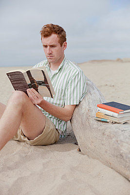 Man reading on beach - p956m1044294 by Anna Quinn