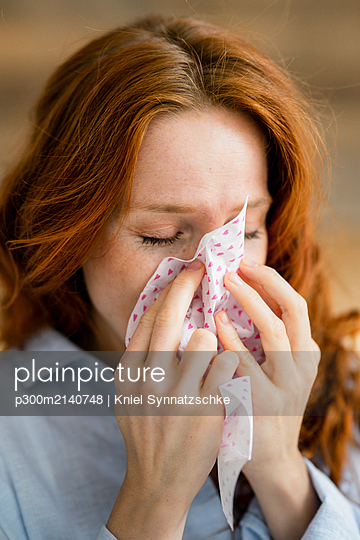 Redheaded woman blowing nose - p300m2140748 by Kniel Synnatzschke