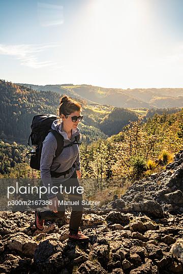 Woman hiking on rocky trail, Karlsruher Grat, Ottenhoefen, Black Forest, Germany - p300m2167386 by Manuel Sulzer