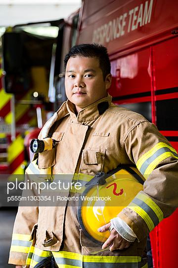 Serious Chinese fireman standing near fire truck