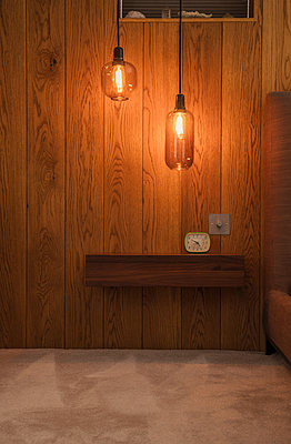 Modern pendant lights hanging over wooden shelf with alarm clock - p1023m2208286 by Tom Merton