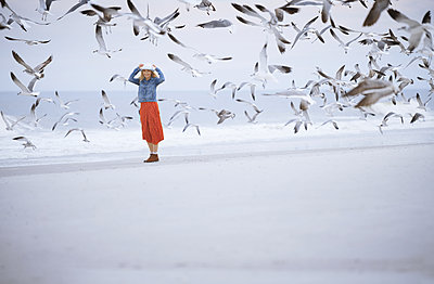 Woman next to the ocean surrounded by flying seagulls - p1577m2150327 by zhenikeyev