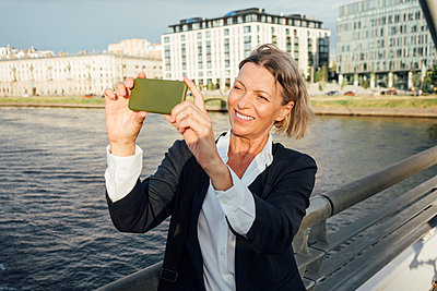 Mature businesswoman photographing through mobile phone by railing in city - p300m2294234 by Vasily Pindyurin