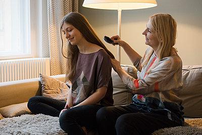 Mature woman brushing daughter's hair at home - p301m1130798f by Halfdark