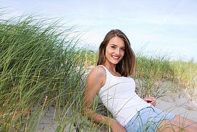 Junge Frau liegt in den Dünen - p341m1480684 von Mikesch
