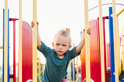 A young girl with blond hair playing in a playground and climbing up a rock ladder on a warm fall day; Spruce Grove, Alberta, Canada - p442m2004262 by LJM Photo