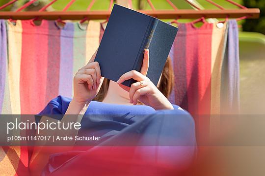 Junge Frau liest ein Buch auf einer Hängematte - p105m1147017 von André Schuster