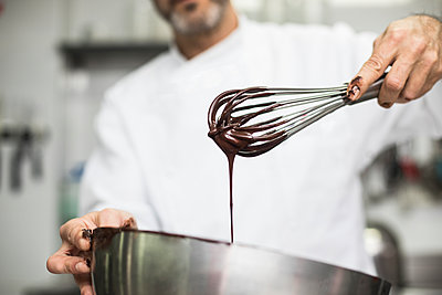 Chef mixing chocolate cream in bowl - p1166m2130242 by Cavan Images