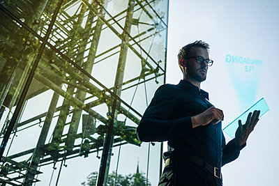 Businessman using futuristic portable device - p300m1356115 by Kniel Synnatzschke