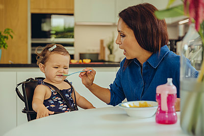 Mother helping disgusted baby daughter eating fruit pulp in kitchen - p300m2042751 von Mareen Fischinger