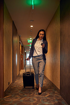 Businesswoman walking in hotel corridor with rolling suitcase - p300m2171407 by Zeljko Dangubic