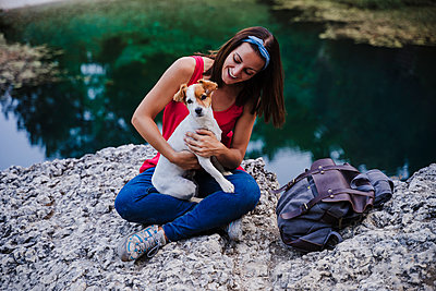 Playful woman holding dog while sitting on rock at lake - p300m2251015 by Eva Blanco