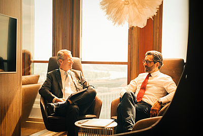 Male lawyers planning while sitting against window at legal office - p426m2127513 by Maskot