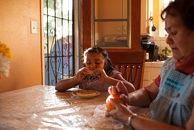 Hispanic grandmother and granddaughter eating in kitchen - p555m1409588 by Shestock