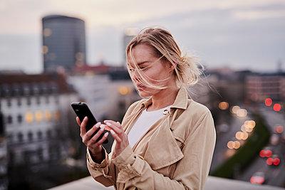 Junge Frau mit Smartphone auf einem Hausdach - p890m2231040 von Mielek